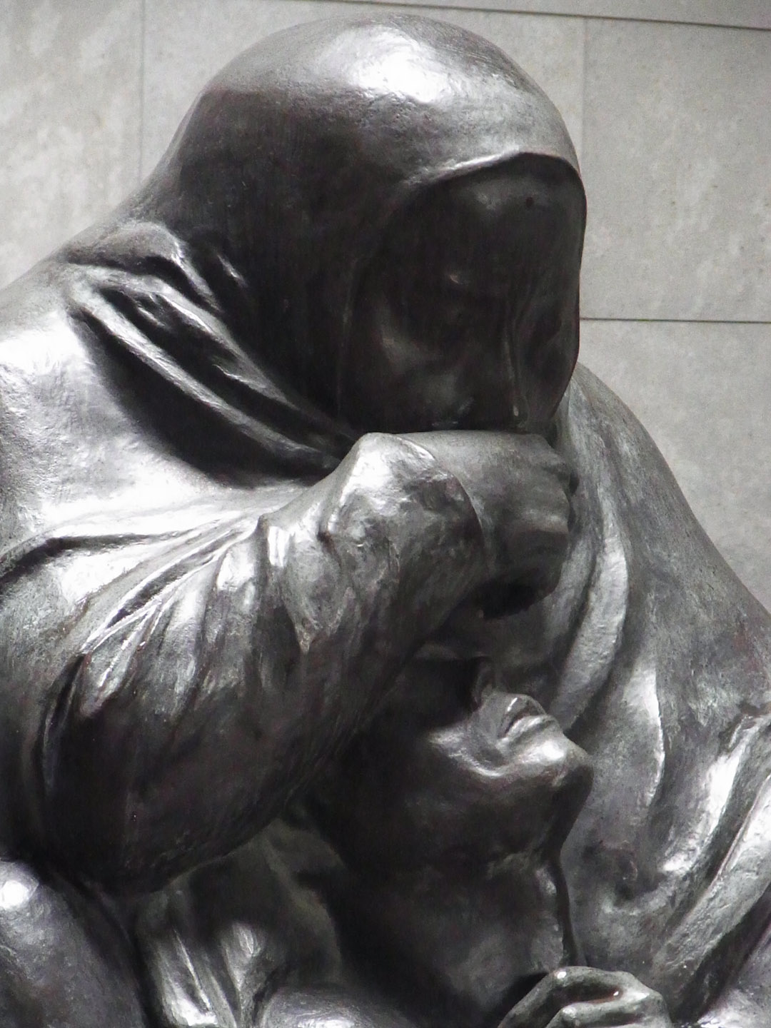 "After German reunification, the Neue Wache was again rededicated in 1993, as the ""Central Memorial of the Federal Republic of Germany for the Victims of War and Dictatorship."" At the personal suggestion of Chancellor Helmut Kohl, the GDR memorial piece was removed and replaced by an enlarged version of Käthe Kollwitz's sculpture Mother with her Dead Son. The pietà-style sculpture is directly placed under the oculus, and so is exposed to the rain, snow and cold of the Berlin climate, symbolizing the suffering of civilians during World War II."